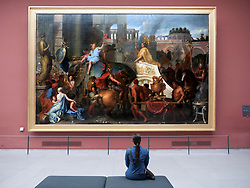 Woman looking at painting Entree d'Alexandre dans Babylone on L'Triomphe d'Alexandre by Charles Le Brun  at The Louvre museum in Paris France