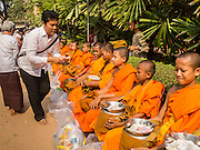 15 MARCH 2015 - SIEM REAP, SIEM REAP, CAMBODIA: A man makes merit by giving Buddhist monks and novices money at the annual mass merit making at Wat Bo in Siem Reap. More than 1,200 Buddhist monks, from across Siem Reap province, received alms from Buddhist lay people during the morning long ceremony. Wat Bo was originally built to be a the temple for Siamese (Thai) troops when Siem Reap and western Cambodia were controlled by Siam (Thailand). Now Wat Bo is one of the most important temples in Siem Reap.      PHOTO BY JACK KURTZ