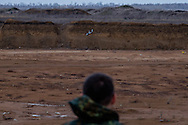 Soldier watching the drone back from its mission over the ennemy position and prepare for landing.