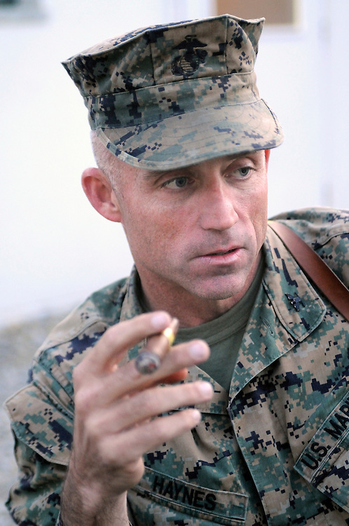 "US Marine Colonel Jeff Haynes, Commanding Officer, 201st Regional Corps Advisory Command, smokes a cigar at Camp Blackhorse.  His senior NCO, Sgt Major Patrick Dougherty, joked, ""Cigars are his only weakness."""