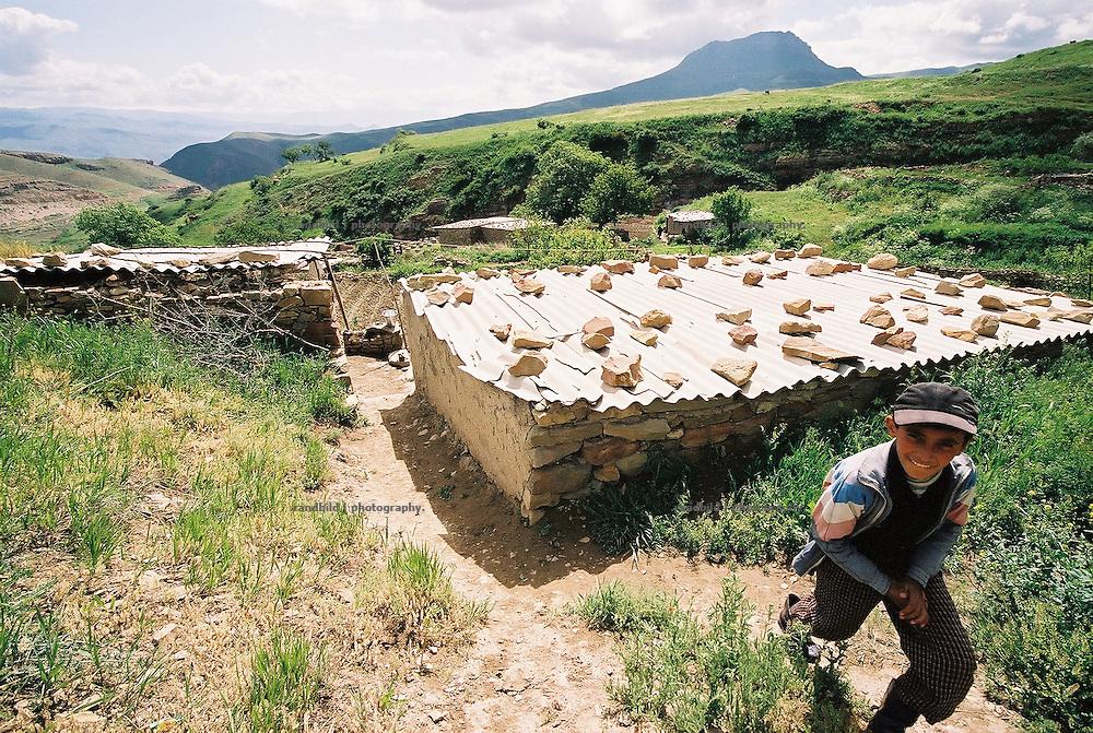 Ein 12-jähriger Junge in seinem Dorf in den abgelegenen Bergen in der Region um die südarmenische Stadt Echegnadzor. Die kleinen Hütten sind aus Bruchstein mit  Wellblechdächern gebaut. a rural mountain village in southern Armenia.