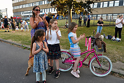 Young family from neighbourhood clapping support for nurses at Thursday 8pm clap for carers during Coronavirus lockdown, Royal Berkshire Hospital, UK May 2020
