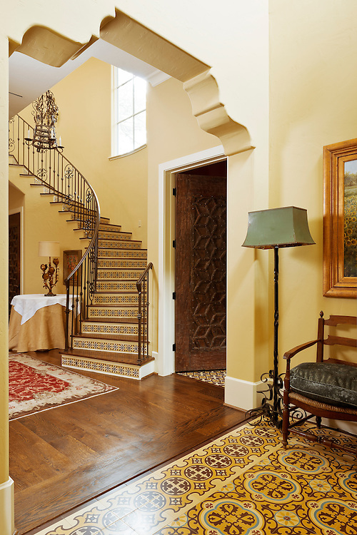 In this residential interior, the homeowner has chosen 3 types of tile to adorn the entry hall floor, ½ bath floor on the right, and the staircase fronts. The tiles as well as the wooden door to the right are all items imported from Morocco.