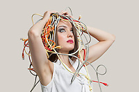 Young woman with head tangled in colorful cables over gray background