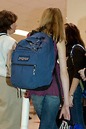 A thin teenage girl carries a very large backpack. Carrying a too-heavy backpack can cause chronic shoulder, neck and back pain, but many school-age children carry huge backpacks everyday. If the backpacks exceed the child's body weight by 15%, or if they carry it on one shoulder, it may be harmful.