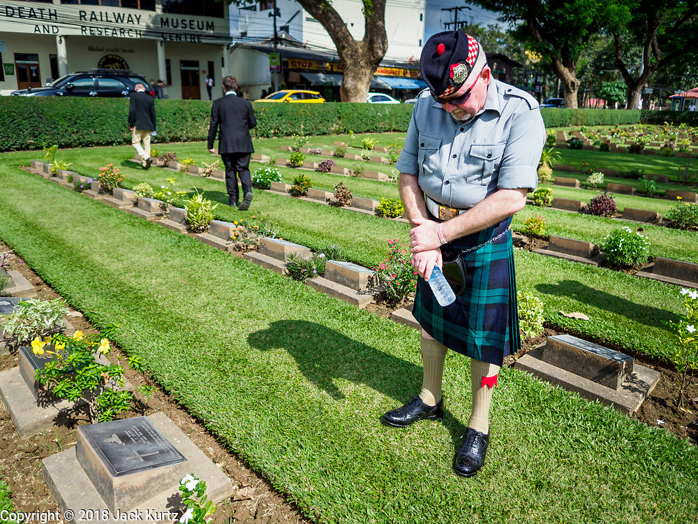 """11 NOVEMBER 2018 - KANCHANABURI, KANCHANABURI, THAILAND: STEWART WILSON, a Scottish veteran of the British army, pauses at the grave of a Scottish soldier killed on the """"Death Railway"""" during the Rememberance Day ceremony at the Kanchanaburi War Cemetery in Kanchanaburi, Thailand. Kanchanaburi is the location of the infamous """"Bridge On the River Kwai"""" and was known for the """"Death Railway"""" built by Japan during World War II using allied, principally British, Australian and Dutch, prisoners of war as slave labor. There are 6,982 people buried in the cemetery, including 5,000 Commonwealth soldiers and 1,800 Dutch soldiers. November 11, 2018 marked the 100th anniversary of the end of World War I, celebrated as Rememberance Day in the UK and the Commonwealth and Veterans' Day in the US.   PHOTO BY JACK KURTZ"""