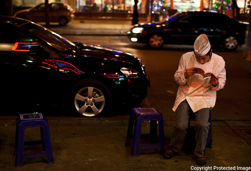 A restaurant worker reads during a break