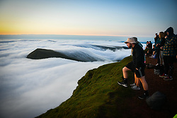 © Licensed to London News Pictures. 08/08/2020. City, UK. A man peers over the edge of a hillside during the morning sunrise from the summit of Pen-y-Fan in the Brecon Beacons, on what is expected to be the hottest day of the year across the UK. The mountain which is the highest in southern Britain, has become increasingly popular with visitors who reach the top of the peak at first light to see the sun rising from the horizon. Photo credit: Robert Melen/LNP