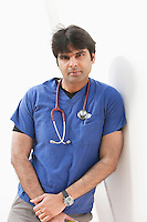 Portrait of an Indian male doctor leaning over white background