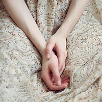 Close up photo of hands in the lap of a girl wearing a light summery dress