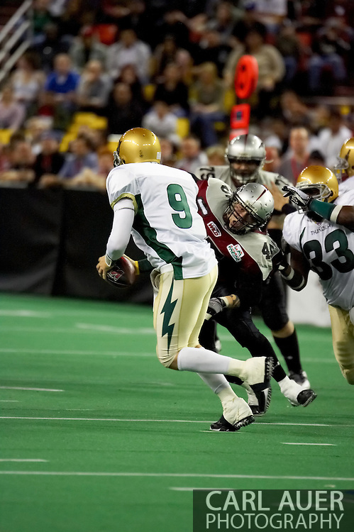 4/12/2007 - Dustin Almond (9) scrambles to get away from Losepa Nicholas-Silvera (45) of the Alaska Wild, as the Fresno Thunder go on to a 46-33 victory over the Wild  in the first professional football game in Alaska.