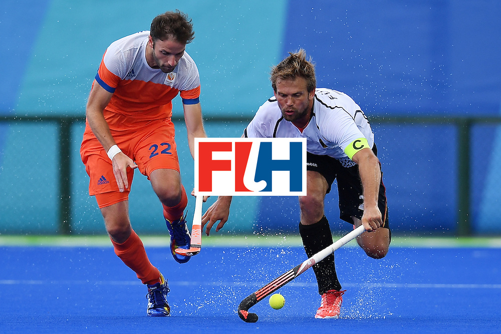 Netherlands' Rogier Hofman (L) and Germany's Moritz Furste during the mens's field hockey Germany vs Netherlands match of the Rio 2016 Olympics Games at the Olympic Hockey Centre in Rio de Janeiro on August, 12 2016. / AFP / MANAN VATSYAYANA        (Photo credit should read MANAN VATSYAYANA/AFP/Getty Images)