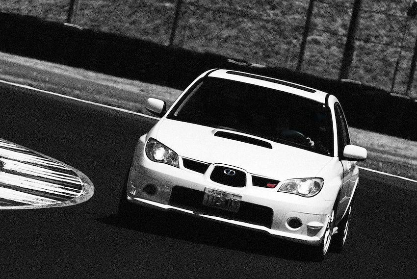 Subaru STi Sport driven by Kit Gauthier, rounding a corner at Portland International Raceway.