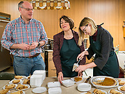 28 NOVEMBER 2019 - DES MOINES, IOWA: US Senator AMY KLOBUCHAR (D-MN), center, with her husband, JOHN BESSLER and her daughter ABIGAIL BESSLER cut pies at the dessert table in the South Des Moines Community Center. Sen Klobuchar served Thanksgiving lunches to people at the center. Sen. Klobuchar is campaigning to be the Democratic nominee for the US Presidency. Iowa holds the first selection event of the Presidential election cycle. The Iowa caucuses are Feb. 3, 2020.               PHOTO BY JACK KURTZ