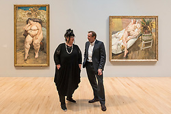 "© Licensed to London News Pictures. 26/02/2018. LONDON, UK. Sue Tilley and David Dawson stand with paintings of themselves by Lucian Freud (L to R) ""Sleeping by the Lion Carpet"", 1996, and ""David and Eli"", 2003-4. ""Preview of ""All Too Human"", an exhibition at Tate Britain which explores how artists in Britain have stretched the possibilities of paint in order to capture life around them.  The exhibition runs 28 February to 27 August 2018 and includes rarely seen works by Lucian Freud and Francis Bacon.  Photo credit: Stephen Chung/LNP"
