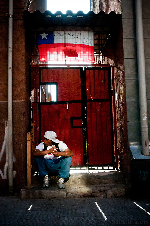 Valparaiso, Chile 2010<br /> <br /> A man sitting under a Chilean flag that reads &quot;Strong Chile&quot; two weeks after the 7.7 earthquake that struck just outside the capital of Santiago.