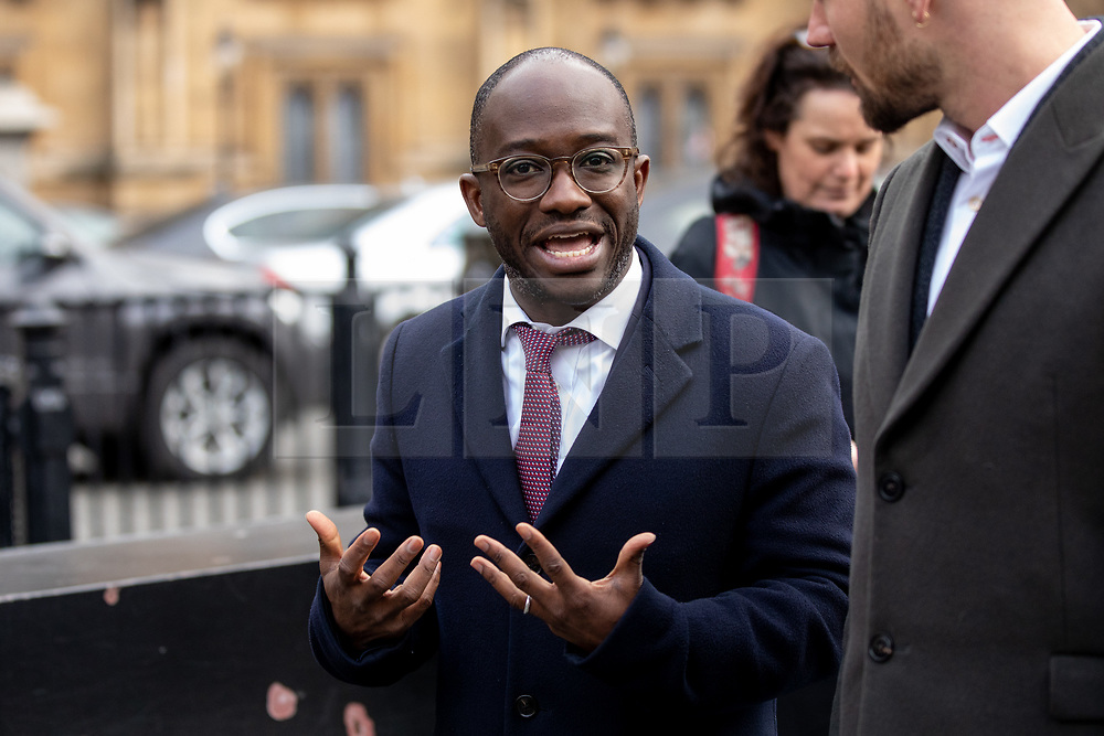 © Licensed to London News Pictures. 15/01/2019. London, UK. Minister of State for Universities, Science, Research and Innovation Sam Gyimah walks through Westminster as pro-Brexit and anti-Brexit demonstrators wave flags and placards next to each outside the Houses of Parliament in Westminster. Today, MPs are due to vote on British Prime Minister Theresa May's EU withdrawal deal, after the previous vote in December was postponed. Photo credit : Tom Nicholson/LNP