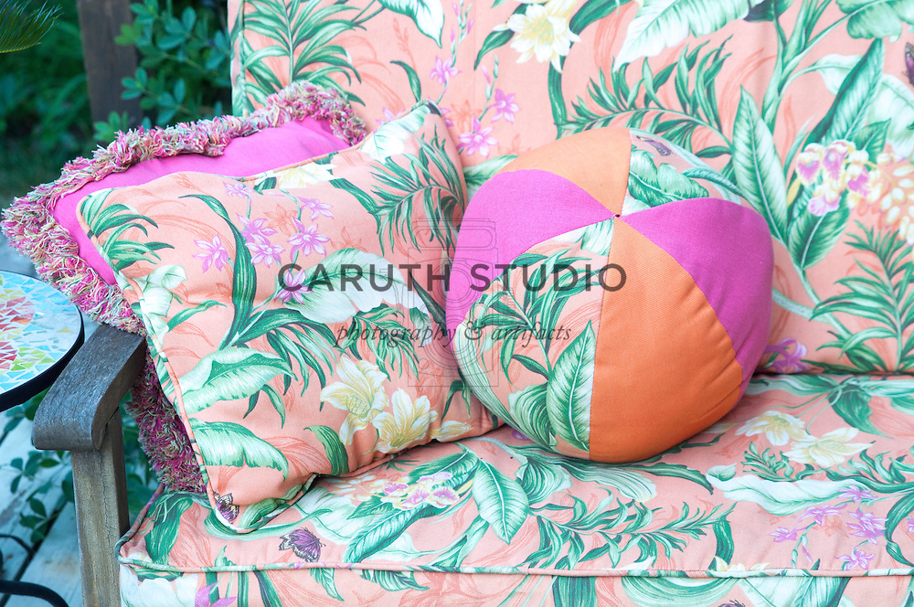 Tropical print cushions on outdoor sofa