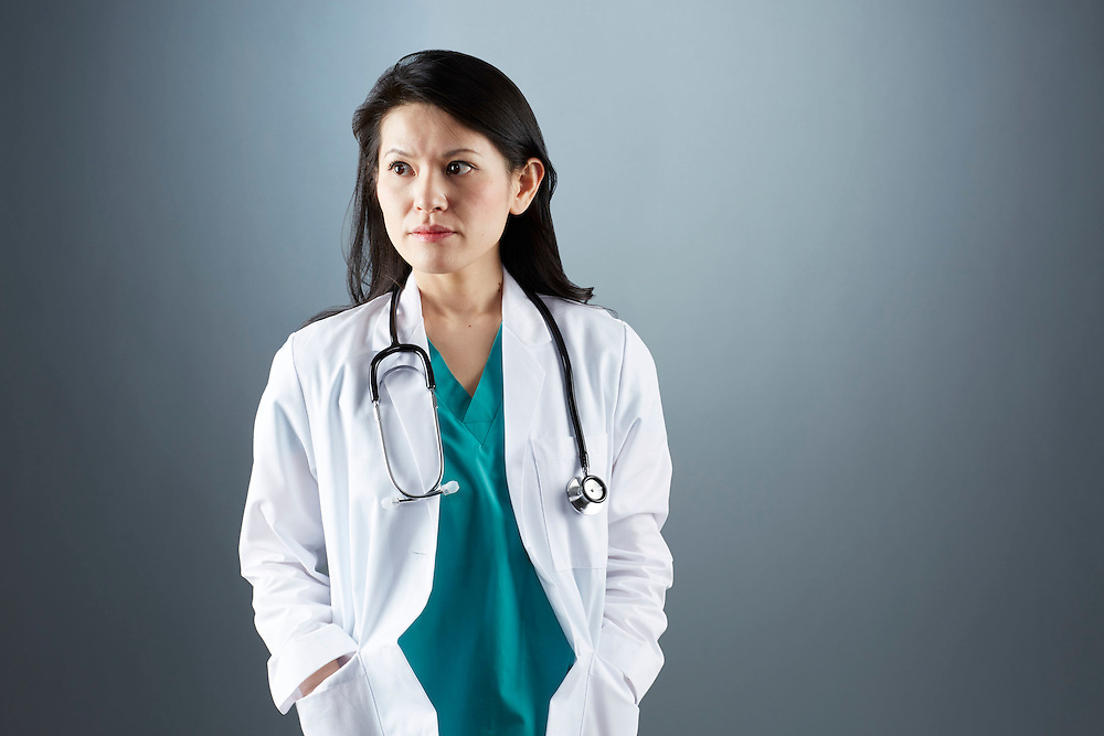 A portrait series representing the intense emotions that Doctors face.  A Japanese female Doctor wearing a white lab coat, stethoscope, and green medical scrub suit shown.