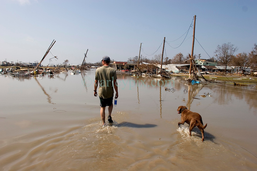 26th Sept, 2005.  Cameron, Louisiana. Hurricane Rita aftermath. <br /> The destroyed remains of a downtown business in Cameron, Louisiana two days after the storm ravaged the small town. local man Aaron Stokes from nearby Carlyss surveys the damage with his dog Maggie.<br /> Photo; ©Charlie Varley/varleypix.com