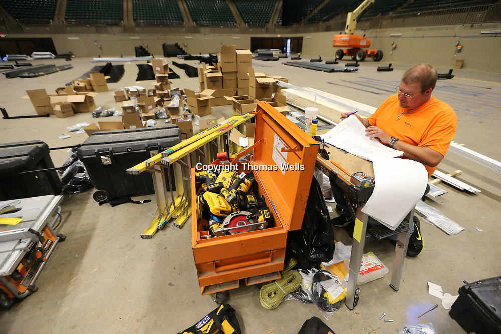 Scott Smith sits in the middle of the BancorpSouth Arena surrounded by all the parts his crew has to assemble to install the new seats in the lower bowl of the arena.