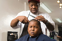Young boy with hair being shaved in the barbers