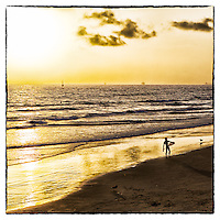 A lone surfer ends mis day at Newport Beach