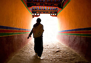 Two traditionally dressed Tibetan women walk down a hallway at Drepung Monastery in Lhasa, Tibet (china)