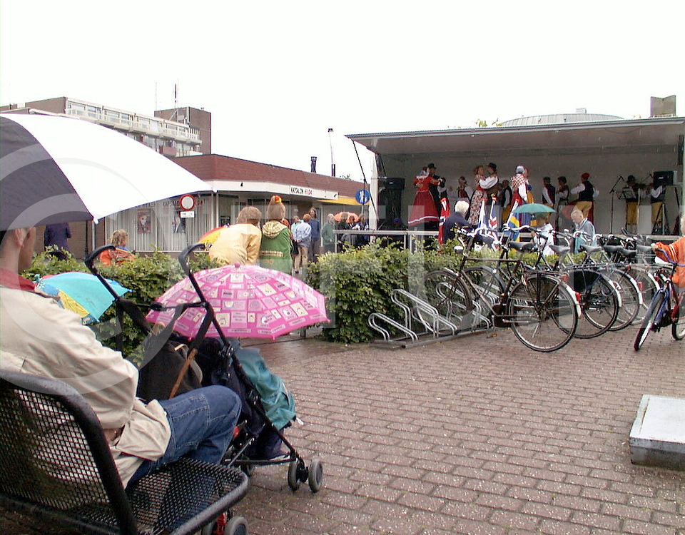 Fotografie Uijlenbroek©1999/Frank Uijlenbroek.990605 hardenberg ned.dansfestival in centrum.groep uit Coevorden dansde onder een luifel in een vrachtwagen terwijl de toeschouwers onder een paraplue schuilde tegen de regen