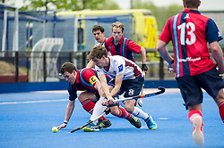 Wimbledon's Chris Gregg gets his shot away while under pressure from Toby Roche of Hampstead & Westminster. Wimbledon v Hampstead & Westminster - Semi-Final - Men's Hockey League Finals, Lee Valley Hockey & Tennis Centre, London, UK on 22 April 2017. Photo: Simon Parker
