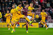 Ricki Lamie (#5) of Livingston FC and Craig Sibbald (#10) of Livingston FC attempt to sandwich Steven MacLean (#18) of Heart of Midlothian FC  during the Ladbrokes Scottish Premiership match between Heart of Midlothian FC and Livingston FC at Tynecastle Park, Edinburgh, Scotland on 4 December 2019.