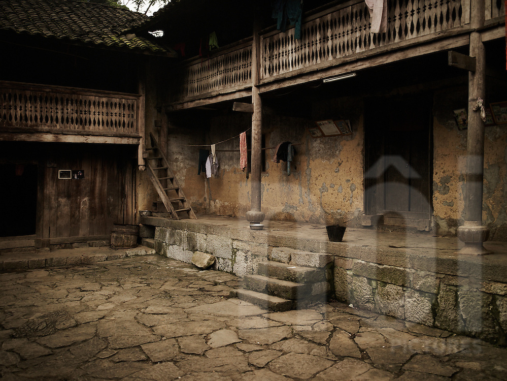 Yard of an old house with wooden columns and rammed earth walls. Ha Giang province, Vietnam, Asia