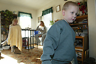 Austin wanders into the living room as his mother talks with a family friend. The disorder has left Austin with almost complete loss of vision and hearing. Austin can navigate through the living room since he knows the layout, but he rarely walks anywhere on his own.