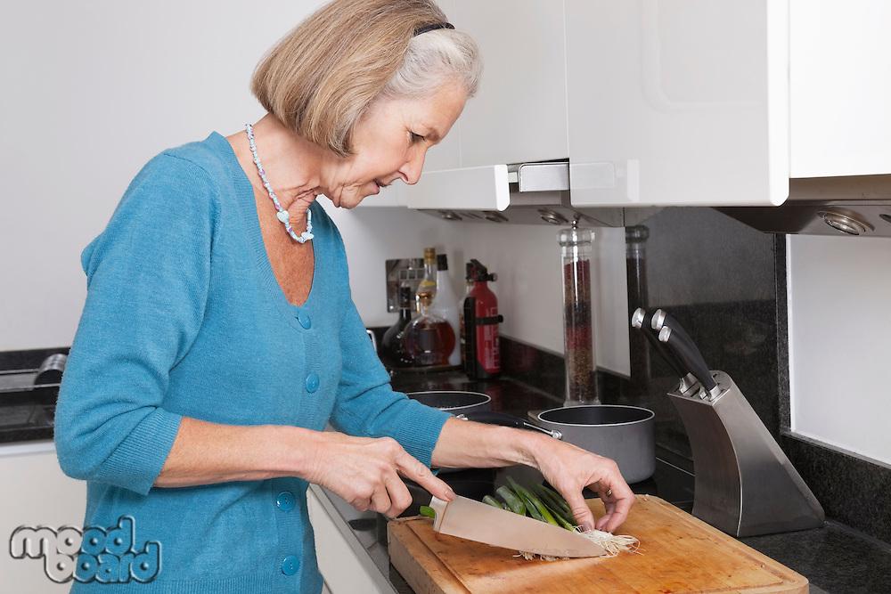 Senior woman chopping vegetables at kitchen counter