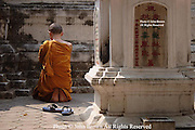 A Buddhist monk kneels in prayer at the base of a stupa at Wat Gate Khar Rnam temple in Chiang Mai, Thailand.