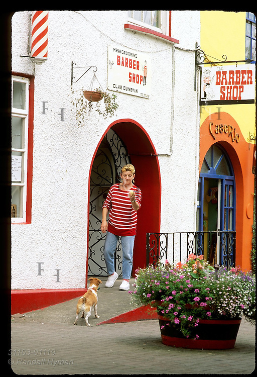 Dog plays catch with its owner, Ann Wakelin, outside barber shop in the town of Kinsale, County Cork, Ireland.