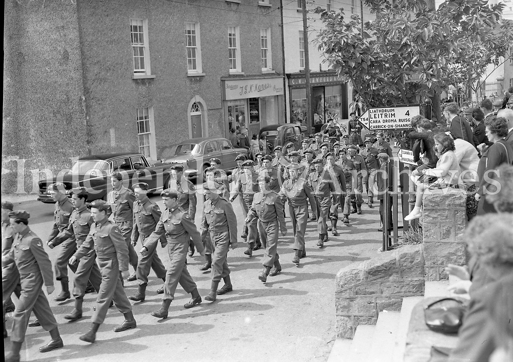 Watching the Toastal Parade, Drumshanbo Co. Leitrim. FCA men parade down the street.<br /> 07 June 1964.<br /> (Part of the Independent Newspapers Ireland/NLI Collection)