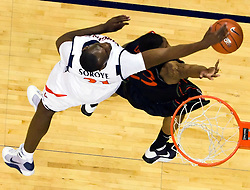Virginia center Tunji Soroye (21) blocks a shot by Miami (FL) guard James Dews (23).  The Virginia Cavaliers fell to the Miami Hurricanes 62-55 at the John Paul Jones Arena on the Grounds of the University of Virginia in Charlottesville, VA on February 26, 2009.