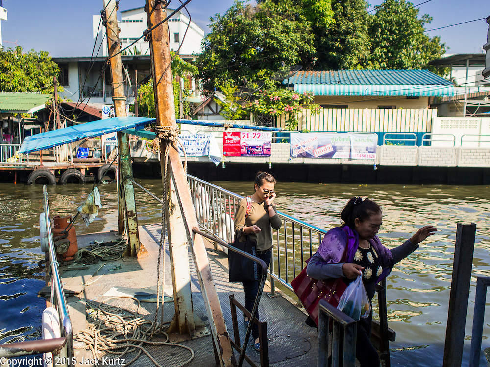 19 JANUARY 2015 - BANGKOK, THAILAND: Passengers get off the ferry on the Sukhumvit side of Khlong Saen Saeb. The small ferry crosses Khlong Saen Saeb throughout the day. It is powered by an diesel engine that uses a system of cables to pull the ferry the 30 feet across the canal. It's used by pedestrians  who need to get across the khlong. The nearest bridge is about ½ mile away.     PHOTO BY JACK KURTZ