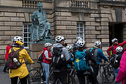 Cycling tourists listen to their guide beneath the statue of philosopher David Hume (1711 -1776), in Edinburgh, on 25th June 2019, in Edinburgh, Scotland. Completed in 1995 by sculptor Sandy Stoddart, it is situated in front of the High Court Building (formally the Sheriff Court) on the Royal Mile.