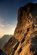 Sunrise Alpenglow warms the basalt cliffs of Beacon Buttress 3121m (10,240 ft), also known as Western Buttress, with Eastern Buttress 3047m (9,996 ft), Devil's Tooth 3019m (9,902 ft) and Inner Tower 3044m (9,986 ft). Ukhahlamba-Drakensberg Park, KwaZulu-Natal, South Africa.  Nikon F90, 24/2.8D. Fuji RDP. September 1994