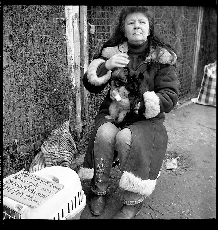 Bazar Olimpia in Warsaw, Poland, February 2008. A woman selling puppies..Every Sunday Morning homeless, alcoholics and unemployed people gather at the so-called Bazar Olimpia to expose on the bare ground their poor things and try to sell them.