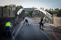 © Licensed to London News Pictures . 09/07/2013 . Manchester , UK . Fire crew clear hoses ready to reopen the bridge .The Barton Road Swing Bridge which links Redclyffe Road and Barton Road over the Manchester Ship Canal , was stuck open today after heat caused the metal frame to expand whilst it was opened to allow a boat to pass beneath . A fire crew doused the metal structure with water to cool it down until it contracted sufficiently to allow the bridge to swing closed . Rush hour traffic backed up for several miles around the Trafford Centre and M60 as a consequence of the road's one-and-a-half hour closure . Photo credit : Joel Goodman/LNP Video available here.. http://www.youtube.com/watch?v=ySGwDNzhH8o