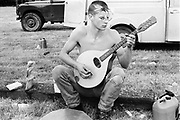 Boy playing the mandolin, at Glastonbury, 1989.