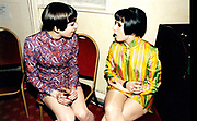 Two young women wearing mini dresses sitting and talking together.