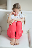 Young girl crying while sitting on sofa