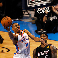 Jun 14, 2012; Oklahoma City, OK, USA;  Oklahoma City Thunder point guard Russell Westbrook (0) shoots against Miami Heat small forward LeBron James (6) during the fourth quarter of game two in the 2012 NBA Finals at Chesapeake Energy Arena. Mandatory Credit: Derick E. Hingle-USA TODAY SPORTS