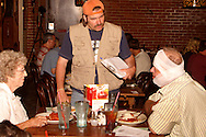 "Jerry Francis as Billy Dutch (standing) talks with Rick Holfinger of Troy during Mayhem & Mystery's production of ""Campground Chaos"" at the Spaghetti Warehouse in downtown Dayton, Monday, July 9, 2012. Holfinger was a 'test subject' for a first aid demonstration during the show."