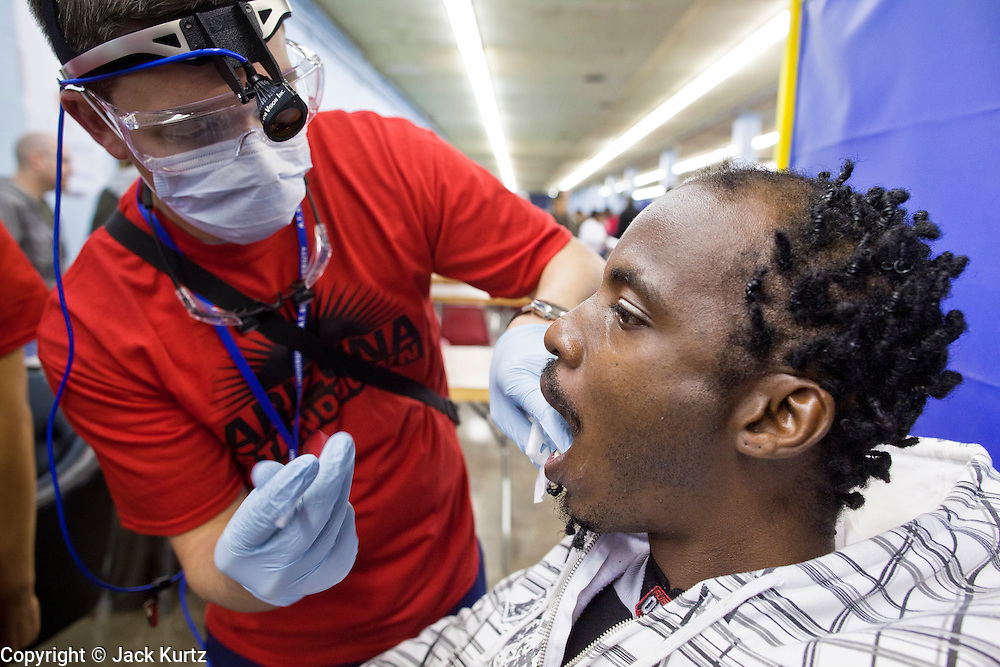 04 FEBRUARY 2011 - PHOENIX, AZ: THAD HEIDLEBAUGH, (left) a dental student at the Arizona School of Dentistry and Oral Health, evaluates CHRIS JAMES, a homeless veteran of the US Army at the Arizona StandDown Friday. The Arizona StandDown is an annual three day event that brings together the Valley's homeless and at-risk military veterans, connecting them with services ranging from: VA HealthCare, mental health services, clothing, meals, emergency shelter, transitional and permanent housing, ID/ drivers license's, court services and Legal Aide, showers, haircuts and myriad other services and resources.  Arizona StandDown is held annually at the Veterans Memorial Coliseum at the Arizona State Fairgrounds in Phoenix on Super Bowl weekend.    Photo by Jack Kurtz