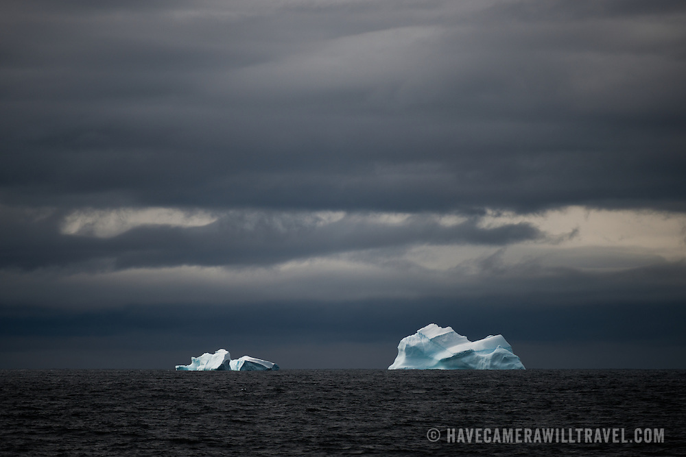 Two blue icebergs float on the horizon against dark skies in Antarctica.